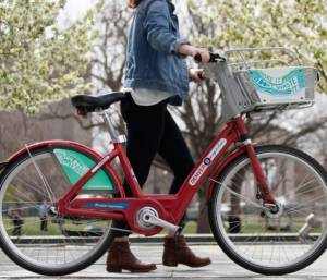 A woman with a jean jacket and black jeans walking a B-cycle bike with a circuit media green graphic on the basket